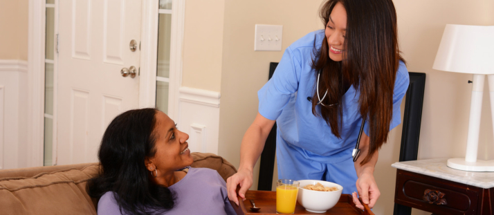 caregiver serving food to her patient