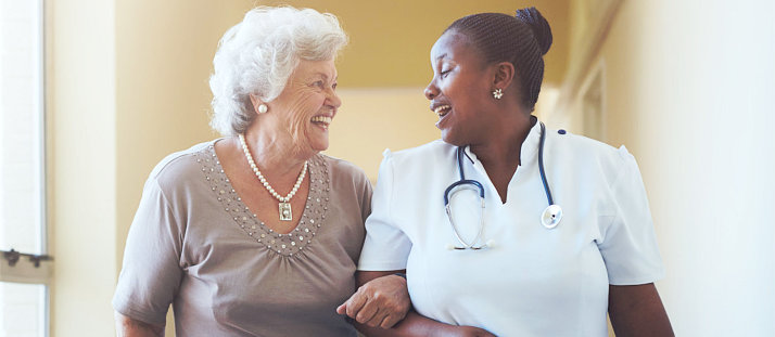 elderly woman and private nurse smiling each other
